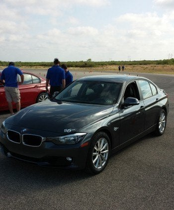 The BMW equipped with Cooper CS5 Ultra Touring tires.  The Cooper Tires Team (seen in the background) attended to the cars and track after each run.  The red 3 Series, also seen in the background, had the Pirelli  Cinturato P7 tires.  This experience reminded me of something out of National Geographic.  The second an animal is born into the wild, predators arrive.  The CS5 is like that – released into the wild and already Pirelli looks to attack.