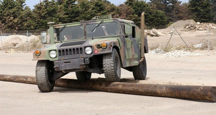 Humvee crossing telephone pole