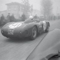 "Mille Miglia May 1 and 2, 1954 Klem photographs former World War II prisoner Luigi ""Gino"" Valenzano's Lancia D24 (0009) from Parnell's DB3S in the early morning fog of the Mille Miglia. Valenzano (1920 –2011), who had known Gianni Lancia from childhood, drove for Lancia at Sebring in 1954 where he finished 2nd, sharing a car with the notorious playboy Porfirio Rubirosa, but would later crash out here. He continued competing the following year for Maserati but retired from racing after his brother Piero was killed during the 1955 Coppa d'Ore delle Dolomiti. Parnell/Klemantaski meanwhile would also crash out, near l'Aquila, without injury."
