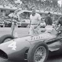 Italian GP Monza September 11, 1955 A smiling Eugenio Castellotti and mechanics walk the Ferrari 555 Squalo (555-4) to his 4th-place grid position as the omnipresent and camera-bedecked Bernard Cahier approaches. The Italian finished an impressive 3rd after the Moss Mercedes Benz W196 streamliner expired, better than the rest and all of them powerless in the face of Mercedes Benz superiority.