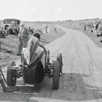 Lewes Speed Trials August 21, 1937 Klemantaski's shot of a young boy holding the chock as a competitor prepares to blast off gives a good idea of the slightly curved and uneven roadway of the Lewes course. Note the car's twin Brooklands fishtail exhaust ends and the exposed spectators.