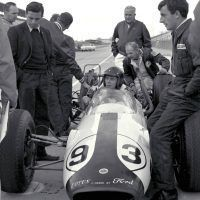 Dan Gurney in Lotus-Ford No. 93, testing at Indianapolis Motor Speedway. Looking on are Jim Clark, Colin Chapman, and Ford Special Vehicles executives. Gurney qualified to start in twelfth position at 149.019 miles per hour. He finished seventh. Ford Motor Company