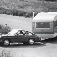 This 1967 base 911 model probably was one of very few ever used to tow a caravan mobile home. The fender mirrors were likely aftermarket accessories. Porsche Archiv