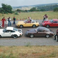 The 1977 model year 911 lineup posed on a Weissach test track curve for a photo. From left, a Turbo 3.0 coupe, a 911S Targa, a Carrera 3.0 coupe, and a base 2.7 coupe. Porsche Archiv