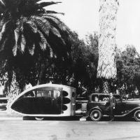 This photo, found in the Airstream corporate archives, depicts an early Airstream trailer, probably circa 1933. Although the man is not identified, it appears to be Wally Byam. The early Airstream trailers used this 'teardrop' design for aerodynamic efficiency. The sleeping compartment was towards the rear of the trailer. There appears to be someone sitting inside the trailer.