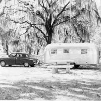 This photo, from the Airstream corporate archives, shows a family enjoying their vacation in style. The car appears to be a circa 1948 Studebaker, and it's towing a large Airstream trailer of the same vintage. Judging by the Spanish moss hanging in the trees we'll say this is somewhere south of the Mason Dixon line