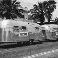 "Wally Byam was a good showman and had a great sense of humor. Here he combined both by showing off two Airstream trailers at once- the larger 'Nursery"" and smaller ""Mother-in-Law"" apartment. Notice the signs in the windows that point out some of the best features of the sturdy Airstreams."