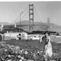 Stopping to pick flowers in San Francisco in 1964, with the Golden Gate Bridge as a backdrop. The car is a 1964 Cadillac, and the trailer is an Airstream Land Yacht.