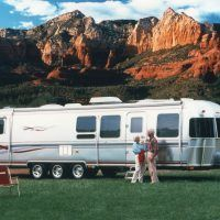 The most luxurious Airstream, the Limited, even came with folding chairs bearing the Limited name. This older couple look very happy as they camp in a lovely spot in view of a majestic range of mountains.