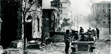 Inside war-torn Europe, probably sometime in 1944: U.S. soldiers enter the bomb-blasted town of Vergato, Italy, about 40 miles southwest of Bologna. The bullet-riddled homes, rubble-filled streets, and blown-out windows testify to the ferocity of the battle to take this town. Note that the tank in the background has a plow blade attached to its front.