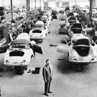 "It was a long way from the converted sawmill in Gmünd to the Porsche factory in Zuffenhausen, but Ferry Porsche (foreground) had been determined to succeed, and by 1960, when this picture was taken, production was racing along. Hardly what one imagines when talking about an ""assembly line"" nowadays, each car still had that personal, almost hand-built quality about it. Photo: Porsche Werkfoto."