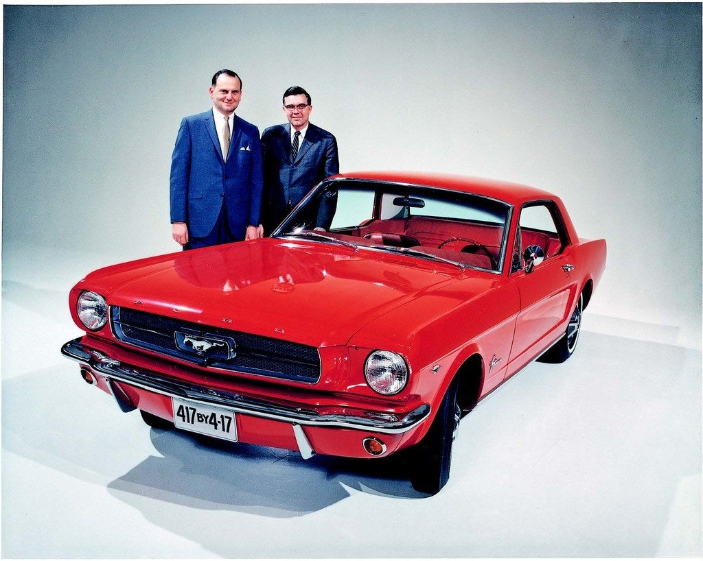 Lee Iacocca (left) and Donald Frey had high hopes for the Mustang in April 1964. As the license plate proclaims, their goal was to sell 417,000 Mustangs by April 17th, 1965, besting Detroit's record for first-year sales of a new model. Photo: Ford Motor Company.
