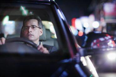 businessman driving at night in the city PRN33NK