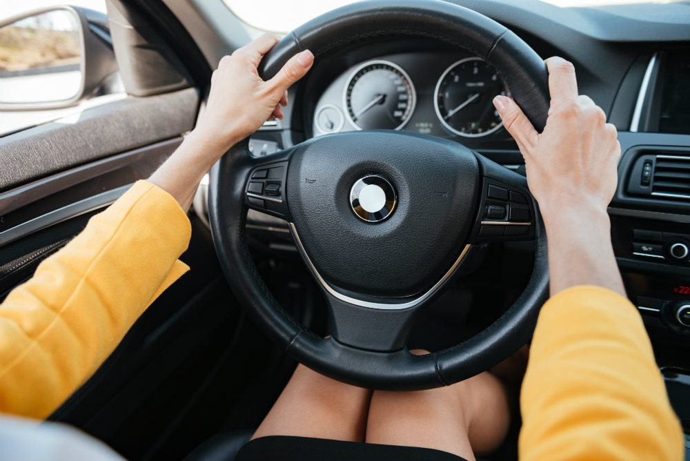 hands holding car wheel and driving PNKLVR2