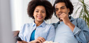 smiling couple with popcorn watching tv at home PD7QCQH 370x180 - Favorite Car Movies By Decade