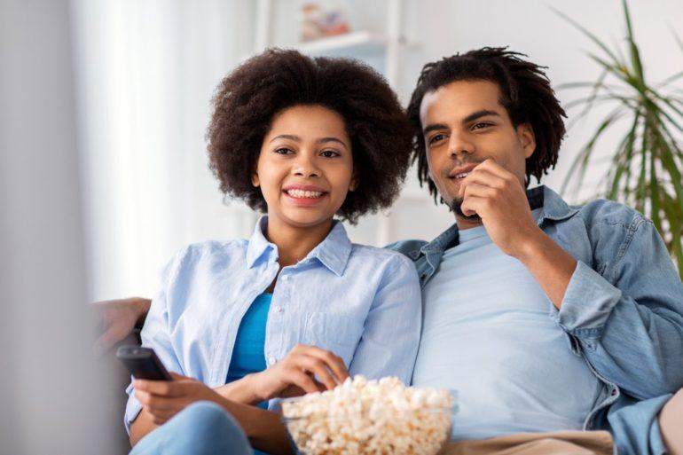 smiling couple with popcorn watching tv at home PD7QCQH