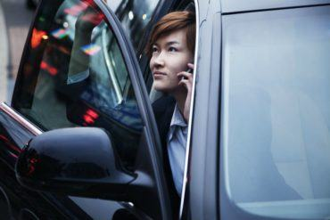 businesswoman exiting car while on the phone PWK4PCR