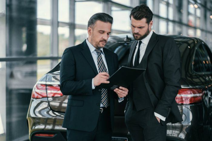 top sales manager and customer at dealership PQZL8UE