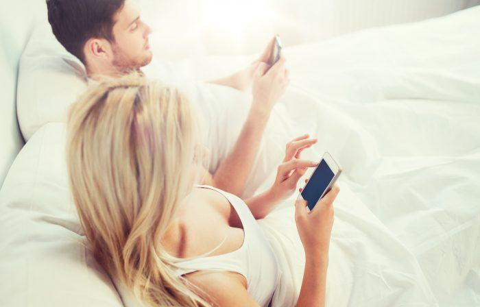 couple with smartphones in bed PWW2E2C