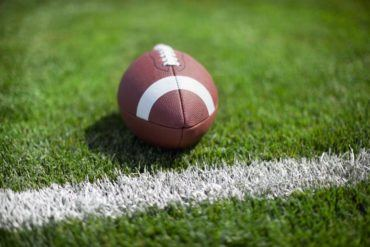 football on grass field with white stripe PF49G68