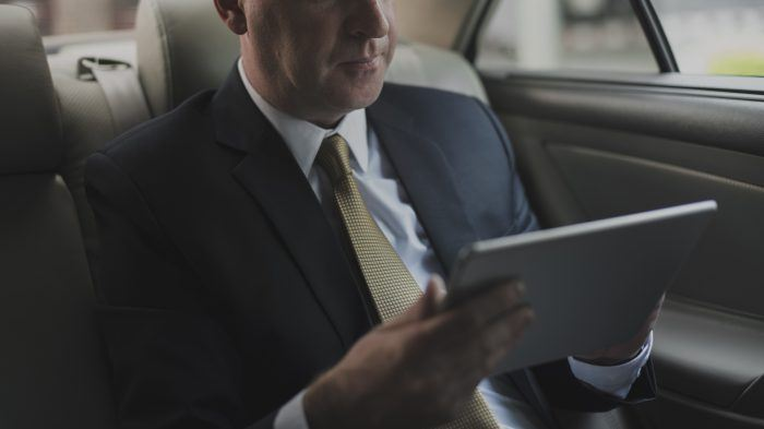Man in car with tablet
