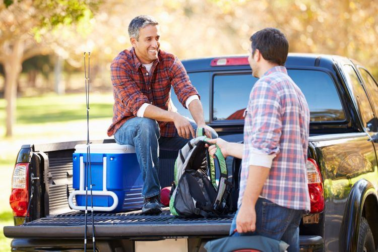two men unpacking pick up truck on camping PRPK5FU 1