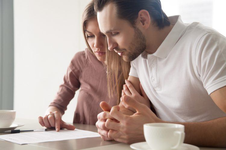 Couple looking at car warranty contract