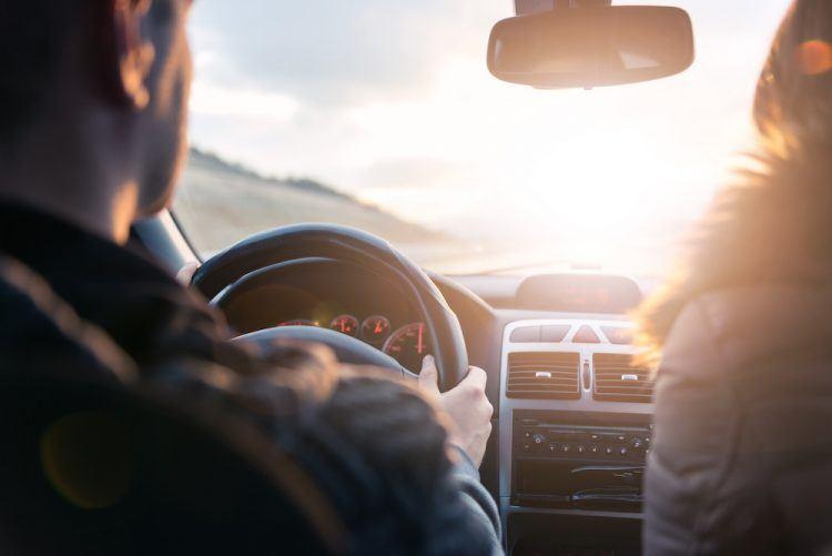 couple driving in car toward sunshine
