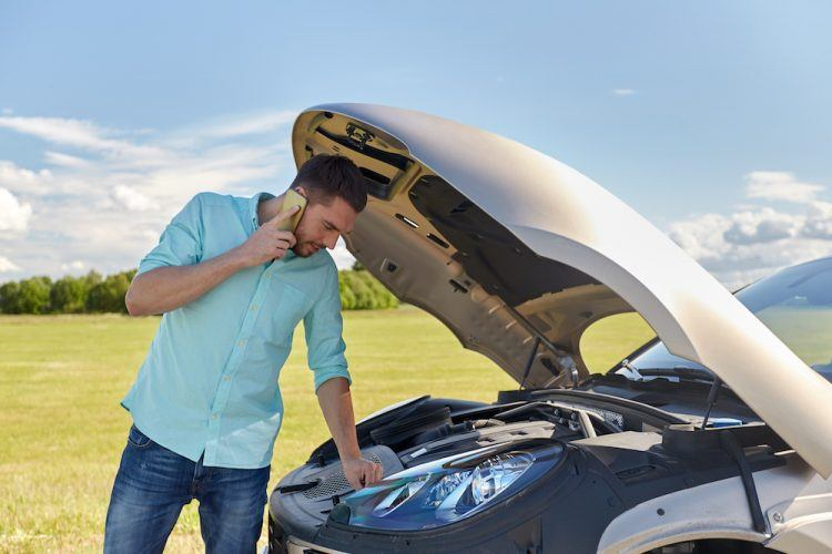 young man with smartphone and open hood of broken car at countryside calling for help
