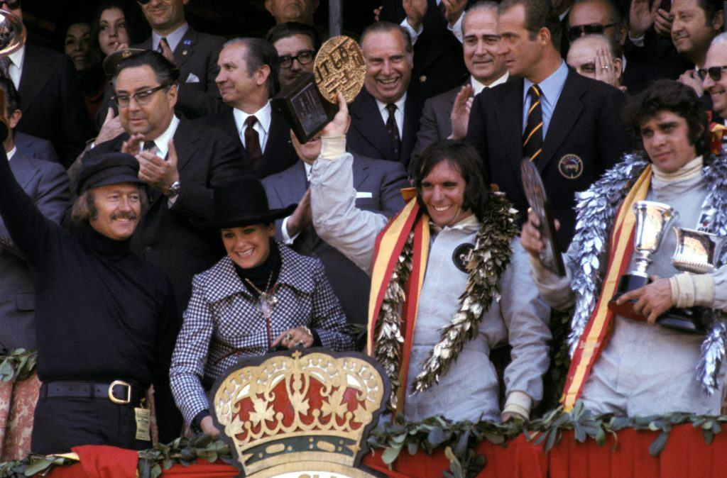 The podium (L to R): Colin Chapman (GBR) Lotus Team Owner; Marie-Helena Fittipaldi (BRA); Emerson Fittipaldi (BRA) Lotus winner; Francois Cevert (FRA) Tyrrell second. Spanish dignitaries in the back include Juan Antonio Samaranch, the provincial political head of Barcelona and member of the International Olympic Committee (IOC) and HRH King Juan Carlos of Spain. Spanish Grand Prix, Montjuich Park, 29 April 1973. From Lotus 72 by Pete Lyons, published by Evro.