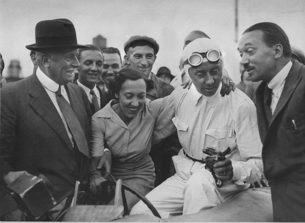 Rene Dreyfus claims the prize on August of 1937. Left to right: Charles Weiffenbach, Chou-Chou, Rene Dreyfus, and Jean Francois. From Faster by Neal Bascomb, published Houghton Mifflin Harcourt.