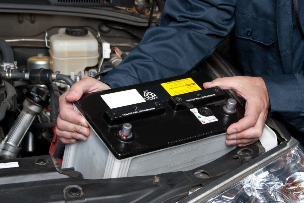 Mechanic replacing a car battery.