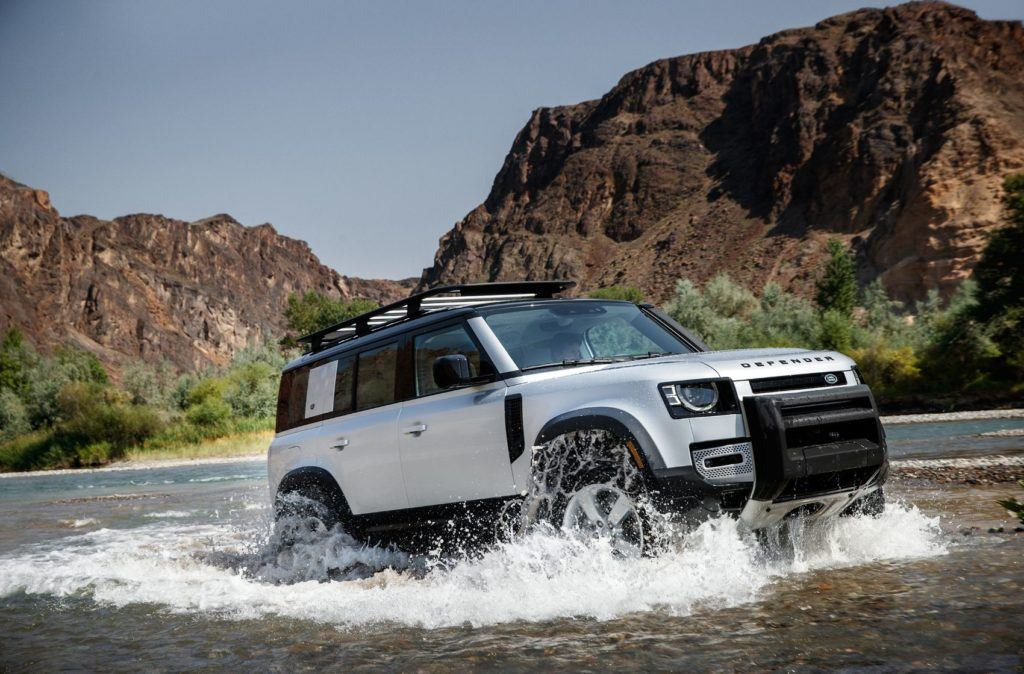 2020 Land Rover Defender driving through water.