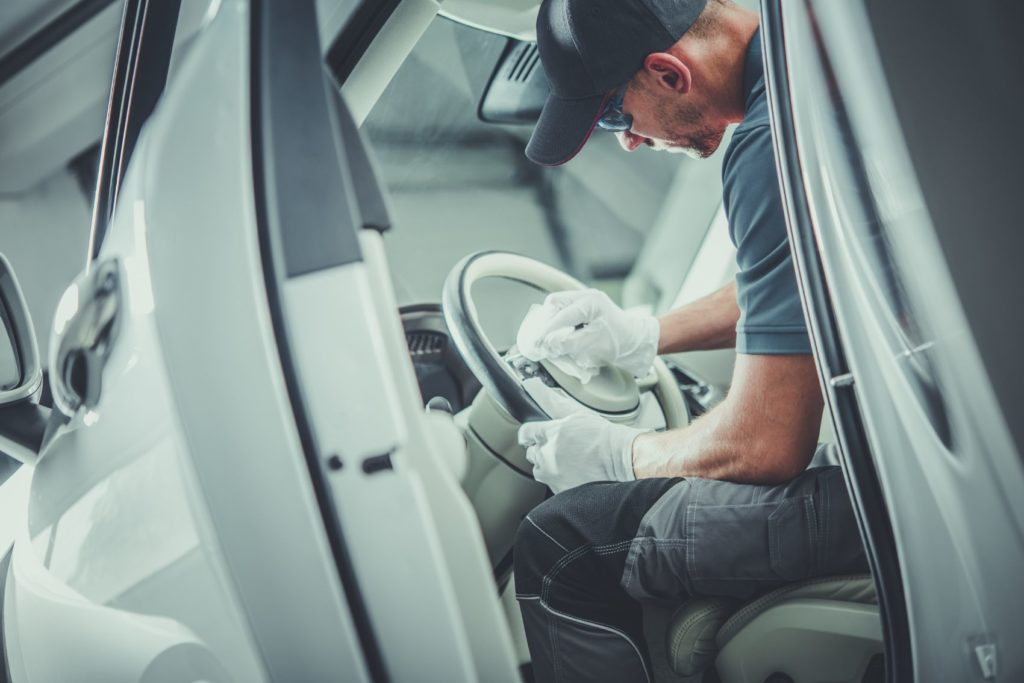 Man detailing the inside of a car.