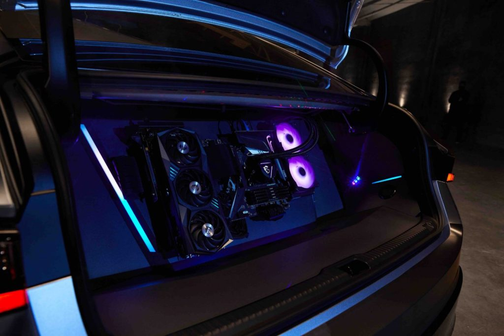 A custom-built gaming PC with an MSI Gaming GeForce GPU + AMD CPU is installed in the vehicle's trunk.