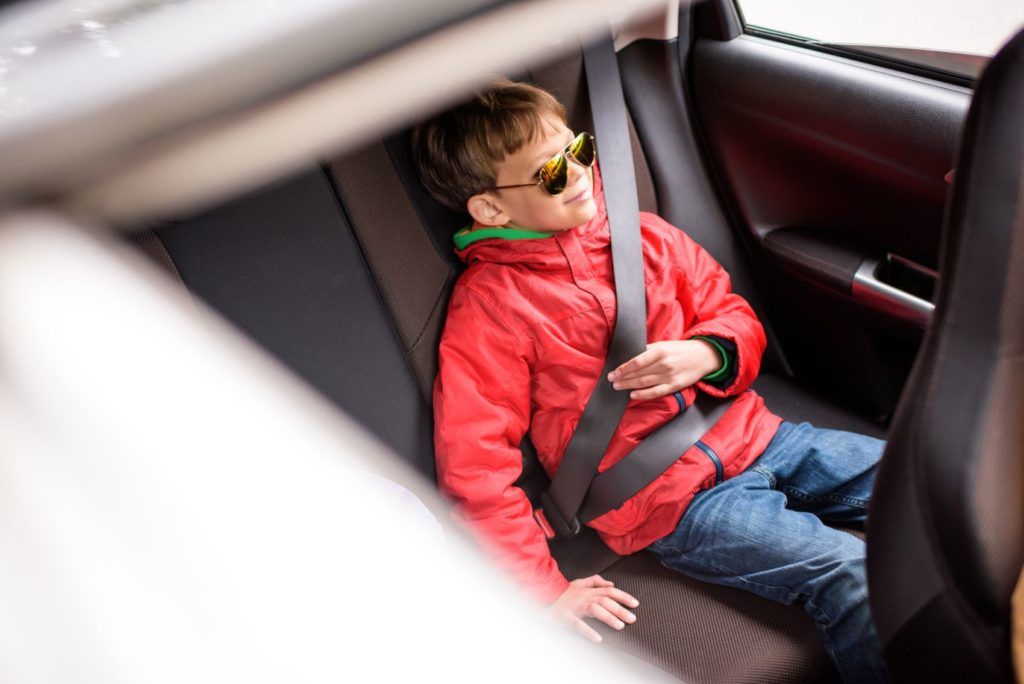 Child riding in a car.
