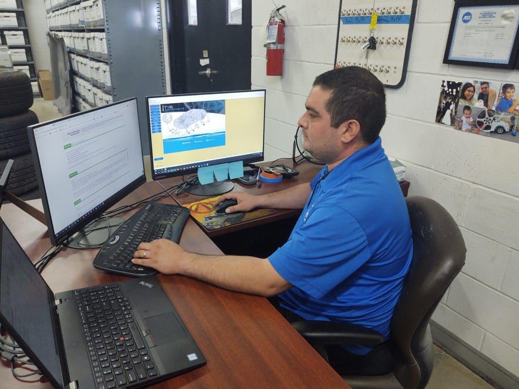 Jose Campos, asTech In-Shop Technician, at his computer.