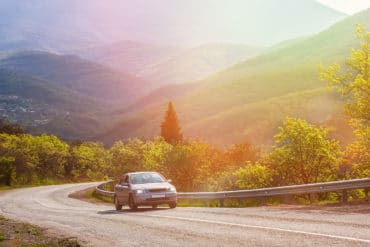 car moves on a mountain road under in the sun