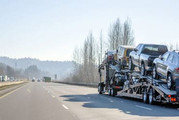 Big rig commercial grade professional car hauler semi truck transporting cars on the special two level semi trailer moving on the straight highway with trees on the hills on the sides