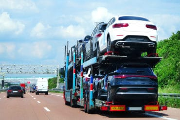 Cars carrier truck transports cars on a highway. Truck transporter